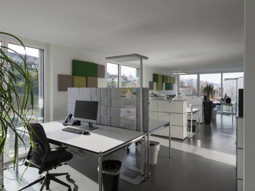 Helles Grossraumbüro der Schaco AG, mit weissen Wänden, hellen Arbeitsflächen und hellgrauem Naturofloor-Bodenbelag. Im Hintergrund, die harmonisch wirkenden Akustikelemente (von Bellton AG) in verschiedenen Grüntönen, an den weissen Wänden.