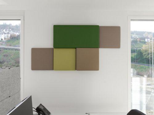 Fünf rechteckige und quadratische Akustikelemente (von Bellton AG), die in verschiedenen Grüntönen, asymmetrisch an einer weissen Wand angeordnet sind.