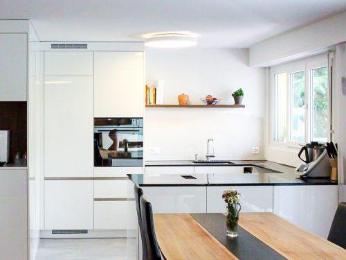 Foto einer frontalen Perspektive vom Wohnraum aus in Richtung Küchenbereich. Im Vordergrund befindet sich ein Esstisch aus dunklem Nussbaumholz, mit einer eingelegten Schieferplatte in der Mitte des Tisches. Im Hintergrund ist die offene Küche zu sehen. Von links nach rechts geschaut, befindet sich ein, in den Wohnraum ragender, raumhoher Einbauschrank an dessen Stirnseite eine Kaffeenische mit einer Jura J600 Kaffeemaschine platziert wurde. Diese Einbausituation wird als Raumtrenner zwischen Eingangsbereich und Küche genutzt. In den Küchenraum blickend befindet sich eine zweiteilige, raumhohe Küchenfront mit einem Kühlschrank und einem Kombi-Steam Backofen von Elektrolux. Rechts der beiden Hochschränke grenzt eine U-Förmige Küchenabdeckung. Die daraus entstandene Kochinsel steht parallel zum Wohnbereich und bildet der Abschluss der offenen Küche. Die Fronten sind in Hochglanzweiss gehalten und die Griffe sind als Griffleisten aus Edelstahl in den Fronten eingelassen. Als Eyecatcher befindet sich über dem Spülbecken ein Wandtablar in Nussbaumoptik.