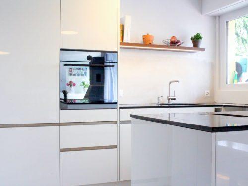 Foto mit Perspektive in den Kücheninnenraum. Im Vordergrund und Zentrum des Bildes befindet sich die Kücheninsel. Im Hintergrund befindet sich die zweiteilige, raumhohe Küchenfront mit einem Kühlschrank und Kombi-Steam von Elektrolux. In der schwarz glänzenden Front des Kombi-Steam Backofens spiegelt sich die gegenüberliegende Kochinsel und der Esstisch wieder, auf dem eine goldene Vase mit rosa Blumen platziert wurde. Weiter rechts neben den beschriebenen zweiteiligen Küchenfronten, grenzt eine U-Förmige Küchenabdeckung mit integriertem Spülbecken und Küchenarmatur. Die Fronten sind in Hochglanzweiss gehalten und die Griffe sind als Griffleisten aus Edelstahl in den Fronten eingelassen. Als Eyecatcher befindet sich über dem Spülbecken ein Wandtablar in Nussbaumoptik.