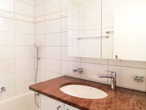 Helles Badezimmer mit Badewanne und Waschtisch dessen Abdeckung aus rötlichem Granit besteht. Die Armaturen und die Garnituren sind verchromt.