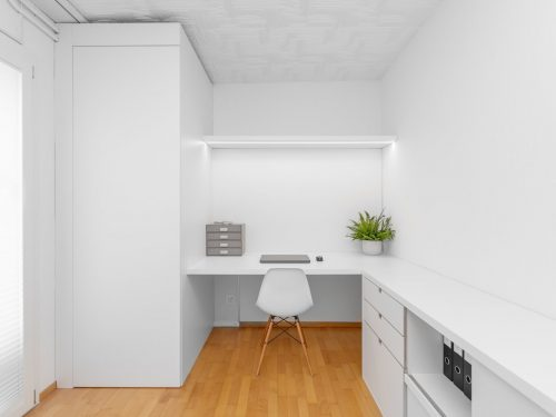 Frontalansicht des neuen Büros. Die neuen Möbel sind alle in weiss gehalten. Links befindet sich ein Raumhoher Schrank, welcher die bestehende Heizung und den Waschtisch verblendet. In der Mitte befindet sich der neue, helle und grosszügige Arbeitsbereich mit einer hellgrauen Ablagebox, einem Laptop mit Maus und einer Topfpflanze auf dem Tisch und einem weissen Stuhl mit Naturholzbeinen Modell Vitra Eames. Entlang der rechten Wand bietet ein Regal mit Schubladen und Ablageflächen Platz für Büromaterial und Ordner.