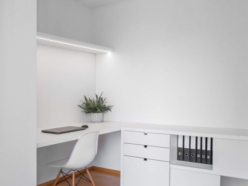 Seitenansicht des neuen Büros. Die neuen Möbel sind alle in weiss gehalten. Links befindet sich ein raumhoher Schrank, welcher die bestehende Heizung und den Waschtisch verblendet. In der Mitte befindet sich der neue, helle und grosszügige Arbeitsbereich. Darauf befindet sich ein Laptop mit Maus und eine Topfpflanze. Als Sitzgelegenheit dient ein weisser Stuhl mit Naturholzbeinen Modell Vitra Eames. Entlang der rechten Wand bietet ein Regal mit Schubladen und Ablageflächen Platz für Büromaterial und Ordner.