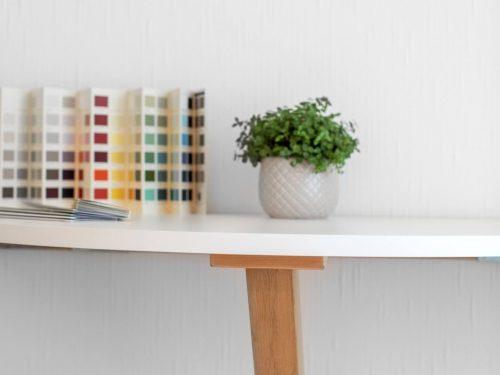 Detailansicht des neuen, an der Wand befestigten halbrunden Klapptisches. Die Tischfläche ist weiss. Ein Balken aus Eiche dient als Ständer, welcher den aufgeklappten Tisch hält. Bei Bedarf kann dieser entfernt und der Tisch heruntergeklappt werden. Auf dem Tisch befindet sich eine kleine grüne Topfpflanze und diverse Farbmuster von Farrow & Ball.