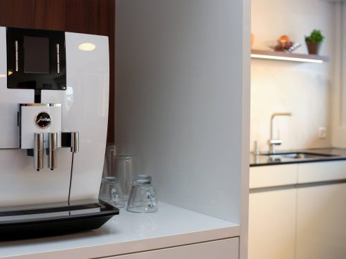 Detailaufnahme der Jura J600 Kaffeemaschine. Die Nische ist in Hochglanzweiss gehalten und als Auflockerung wurde die Rückwand in Nussbaumoptik gehalten. In der Nische steht eine weisse Jura J600 Kaffemaschine mit schwarzem Display. Rechts neben der Kaffeemaschine stehen drei gläserne Espressotassem. Im Hintergrund erkennt man, leicht verschwommen, die Küchenzeile mit Spülbecken und Küchenarmatur und das darüber befestigte Tablar in Nussbaumoptik mit indirekter LED-Beleuchtung.