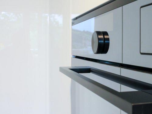 Seitliche Detailaufnahme des Kombi-Steam EB6SL70KSP von Elektrolux. Im Vordergrund befindet sich das Display mit integriertem Drehwähler. Die spiegelnde, schwarze Oberfläche integriert sich perfekt in die hochglanzweisse Küchenfront.