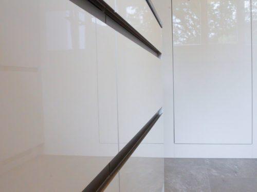 Seitliche Detailaufnahme der Küchenfront. Auf der linken Seite des Bildes erkennt man die in Hochglanzweiss gehaltene Küchenfront mit eingefrästen Griffleisten aus Edelstahl. In der Spiegelung der Fronten kann man leicht die gegenüberliegende Küchenzeile erkennen. Der Boden ist mit gräulich, maserierten Platten in rustikaler Steinoptik versehen.