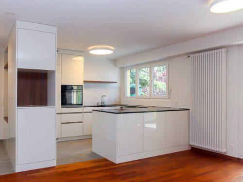 Foto einer Perspektive von Wohnraum aus in Richtung Küchenbereich. Eine offene Küche steht im Zentrum des Bildes. Von links nach rechts geschaut, befindet sich ein, in den Wohnraum ragender, raumhoher Einbauschrank der an dessen Stirnseite sich ein offenes Fach für eine Kaffeemaschine befindet. Diese Einbausituation wird als Raumtrenner zwischen Eingangsbereich und Küche genutzt. In den Küchenraum blickend befindet sich eine zweiteilige, raumhohe Küchenfront mit Kühlschrank und Kombi-Steam Backofen von Elektrolux. Rechts an die beiden Hochschränke grenzt eine U-Förmige Küchenabdeckung. Die daraus entstandene Kochinsel steht parallel zum Wohnbereich und bildet der Abschluss der offenen Küche. Die Fronten sind in Hochglanzweiss gehalten und die Griffe sind als Griffleisten aus Edelstahl in den Fronten eingelassen. Als Eyecatcher befindet sich über dem Spülbecken ein Wandtablar in Nussbaumoptik.