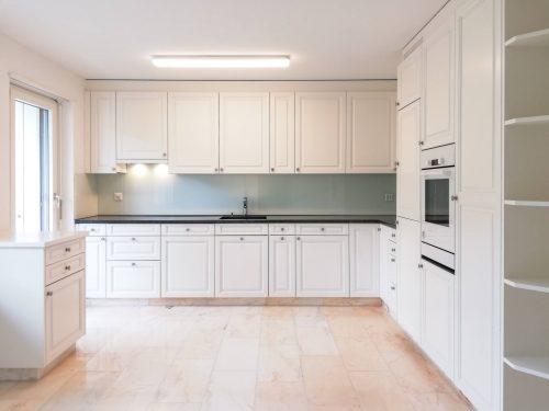 Helle, komplett in weiss gehaltene Küche im Landhausstil mit dunkler Granitabdeckung und verchromten Armaturen. Der Boden ist aus Marmor und die Rückwand aus Glas.