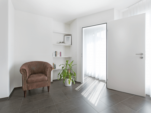 Ansicht der neuen Wand, weiss verputzt. Die neue Tür ist geöffnet. Im Vordergrund stehen der bestehende braune Stuhl und die Topfpflanze. Das Regal im Hintergrund ist mit Büchern und einem Bild dekoriert.