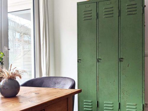 Wohnzimmer mit einem alten Holztisch im Vordergrund. Auf dem Tisch befindet sich eine dunkelviolette runde Vase mit einem Strauss Korn. Auf der Seite des Tisches befindet sich eine Schublade, am Kopf ein dunkler Lederstuhl. Im Hintergrund steht ein alter, grüner, dreitüriger Spind, welcher zu einem Wohnzimmerschrank umfunktioniert wurde.