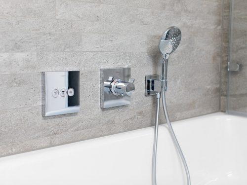 zwei verchromte, eckige Unterputz-Armaturen mit Drucktasten und Thermostat (ShowerSelect von Hansgrohe), die für die Bedienung der Handbrause, dem Brausenkopf von Similor und des seitlichen Wanneneinlaufs, über dem Badewannenrand montiert wurden.