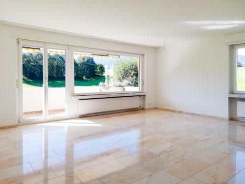 Helles, unmöbeliertes Wohnzimmer mit Zugang zum Balkon, weiss verputzen Wänden und einem Boden aus Marmor.