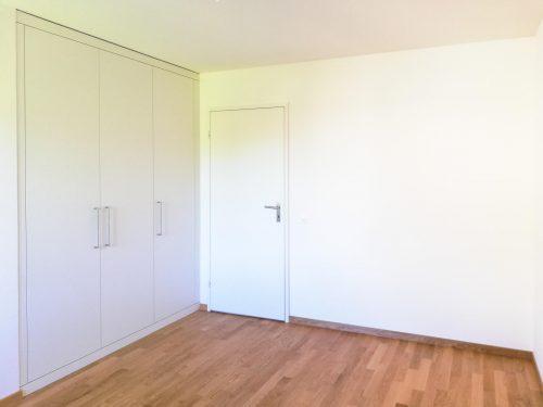 Schlafzimmer ohne Möbel, mit dreitürigem Einbauschrank, naturgeöltem Eichenparkett und weiss verputzten Wänden