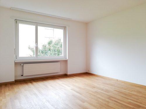 Helles unmöbeliertes Schlafzimmer mit Eichenparkett, naturgeölt und weiss verputzen Wänden.