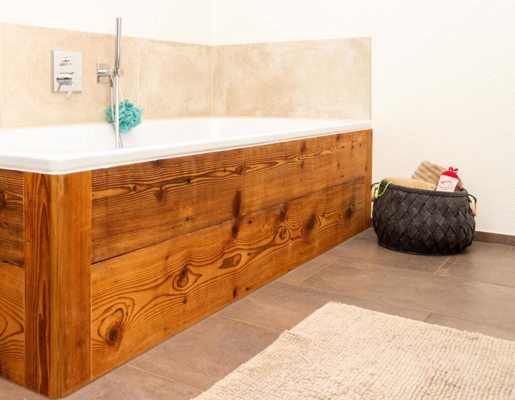 Ausschnitt aus dem Badezimmer auf dem eine eingebaute Badewanne zu sehen ist. Die Badewanne wurde mit dunklem, rustikalem Holz verkleidet. Rechts neben der Badewanne befindet sich ein dunkler, geflochtener Korb in dem beige Handtücher liegen. Über der Badewanne wurde eine beige Plattenreihe als Spritzschutz verlegt. Die Badewannenarmatur wurde unterputz verbaut und hat eine quadratische Abdeckung.