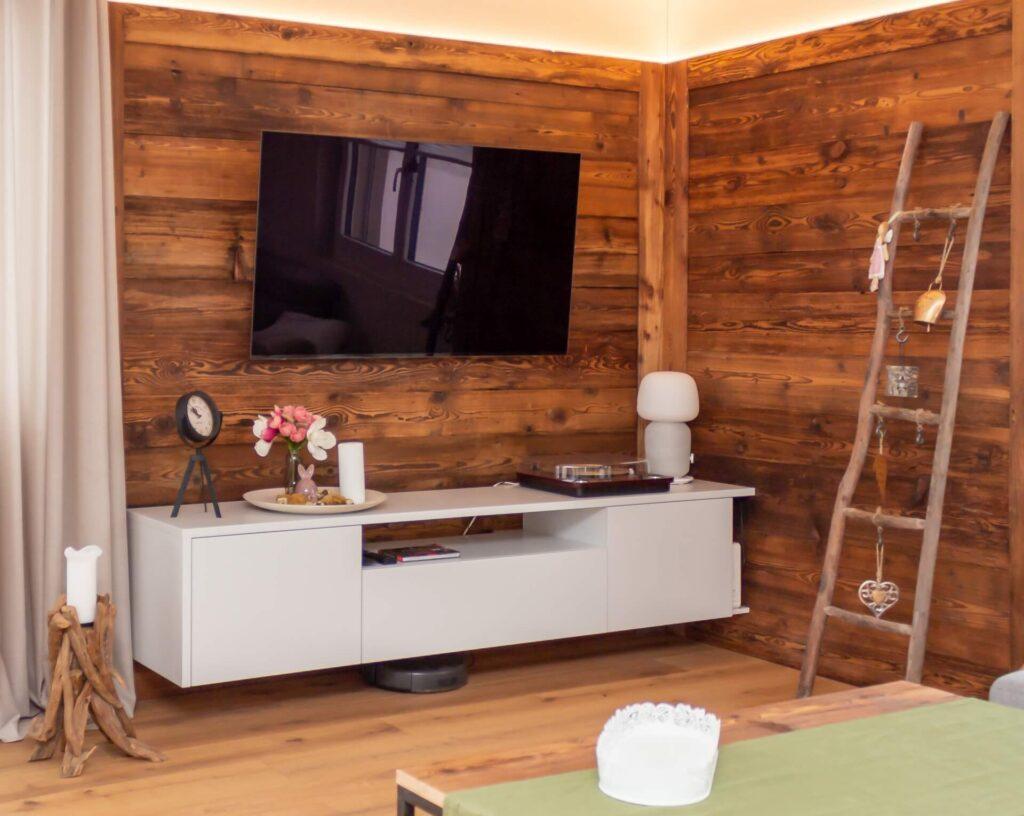 Eine Wohnecke von ca. 250 x 150 cm, ausgekleidet mit einer rustikalen Holzwand aus alten dunklen Balken. Die Holzwand die oberenbereich ein LED- Band eingearbeitet hat, endet ca. 40 cm unter der hell gestrichenen Decke und beleuchtet diese indirekt. An der linken und längeren Seite der Wand wurde ein weisses Sideboard auf die komplette Breite montiert. Darauf sind diverse Dekoartikel wie eine kleine Standuhr, eine Vase in der pinke und weisse Tulpen eingestellt sind, eine weisse Kerze und ein Plattenspieler. Über dem Sideboard hängt ein grosser Fernseher. Weiter rechts, an der der kürzeren Seite der Holzwand, ist eine Alte Holzleiter angelehnt. An den jeweiligen Sprossen hängen verschiedene Glocken, Herzen an Lederbändern und ein rosa Engel. Im Vordergrund wurde ein Salontisch, der aus dem selben Holz besteht wie die Holzwand, in Kombination mit einem moosgrünen Tischläufer platziert.