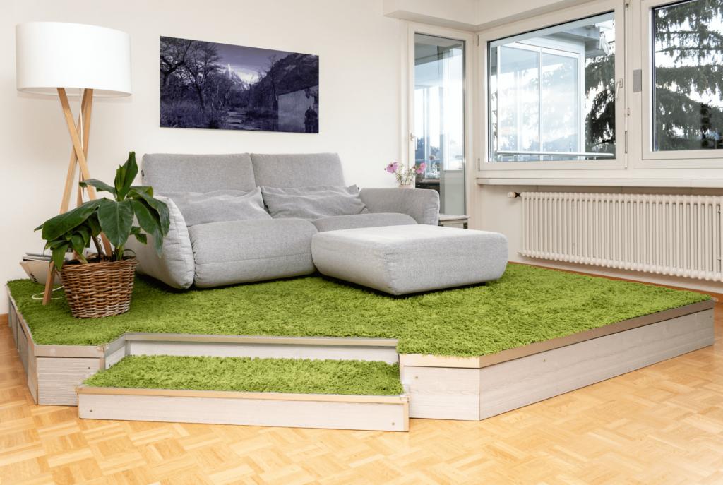 Ansicht des selbst gebauten Podest in der Totalen. Das Podest wurde aus gräulichem, grob gehobelten Holz gebaut und ist ca. 30 cm hoch. Das Podest hat die Form eines abgewinkelten Rechtecks. Im abgewinkelten Teil befindet sich eine Stufe. Podest und Stufe sind mit einem hellgrünen Hochflor-Teppich belegt. Auf dem Podest befindet sich ein hellgraues Doppelsitzer Sofa von Rolf Benz inkl. Fusshocker in der gleichen Farbe. Links vom Sofa steht eine grüne Zimmerpflanze in einem geflochtenen Topf und dahinter eine Stehlampe mit einem Dreibeinigen Ständer aus Holz und rundem Schirm aus hellem Stoff. An der weissen Wand im Hintergrund hängt ein in schwarz / violett gehaltene Fotografie des schneebedeckten Cerro Torre mit verwilderter patagonischer Landschaft im Vordergrund.