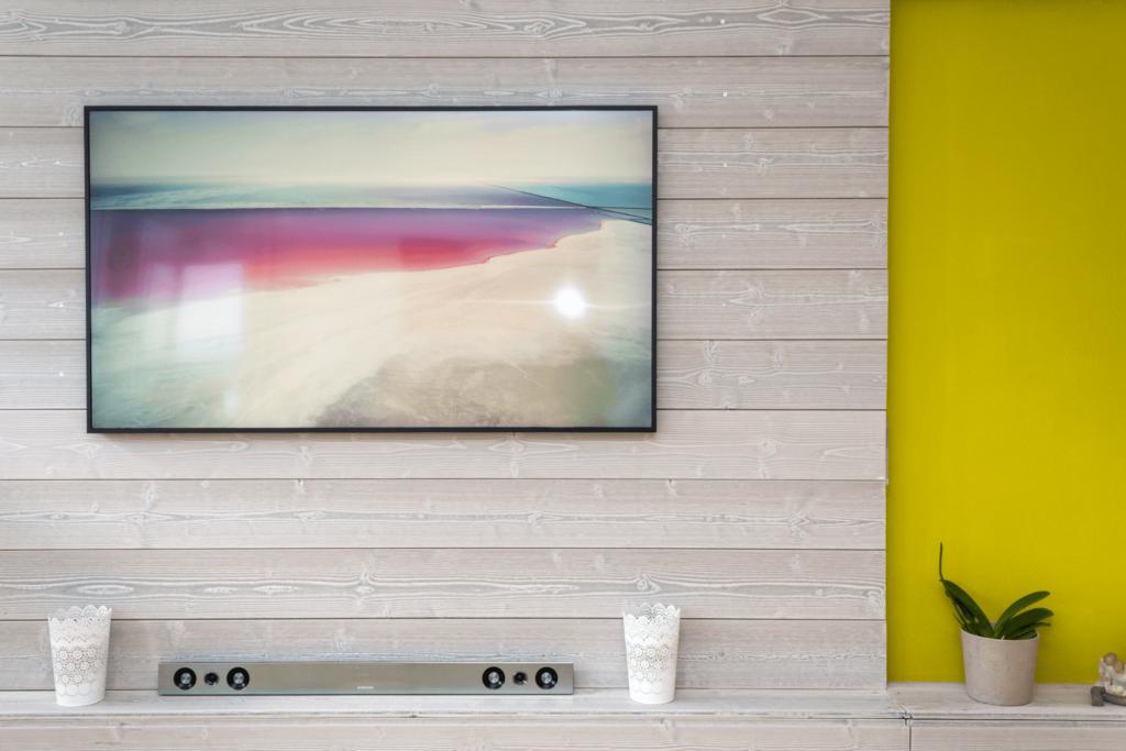 Frontalansicht der mit hellgräulichem, grob gehobelten Holz verkleidete Wand. Die Verkleidung wurde aus querliegenden Brettern (Landhausdielen) erstellt. Als «Bild» hängt ein Fernseher von Samsung, Modell The Frame, an der verkleideten Wand und zeigt eine Küstenlandschaft in Pastelltönen. Unterhalb der Verkleidung befindet sich ein aus dem gleichen Holz erstelltes Sideboard. Darauf befinden sich zwei weissen Windlichter, eine kleine, grüne Pflanze in einem hellen Topf und zwischen den Windlichter eine Samsung HW-D570 Heimkino Soundbar. Als starker Kontrast zum hellen weiss / gräulichen Holz wurde die Wand rechts davon in einem auffälligen hellen und leuchtendem Senfgelb gestrichen.