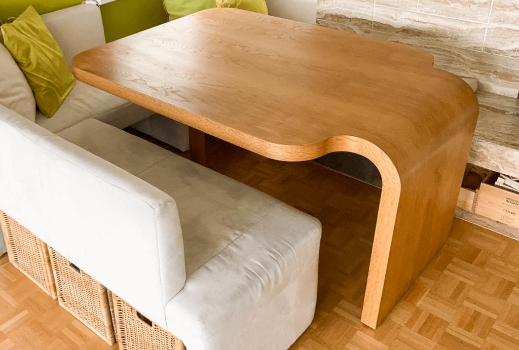 Eckbank mit einem Tisch aus einer Massivholzplatte. Die Tischplatte ist auf der linken Seite abgerundet und geht nahtlos als Tischbein weiter bis auf den Boden. Um den Tisch befindet sich eine weiss bezogene Sitzecke mit grünen Kissen.