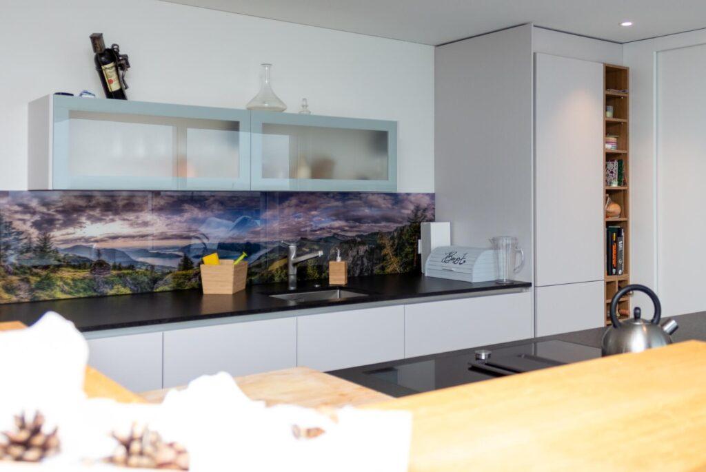 Perspektive in eine offene Küche gerichtet. Im Hintergrund befindet sich eine dunkle und breite Abdeckung die als Arbeitsfläche dient. Als Spritzschutz wurde ein breites Panoramabild hinter Glas montiert. Das in Emmetten aufgenommene Bild, zeigt eine mit Wolken behangene Abendstimmung, mit Aussicht auf den Vierwaldstättersee. Weiter über die rechte Seite gliedert sich ein weisser Hochschrank an die Arbeitsfläche. Um den Platz zwischen Hochschrank und kommende Wand optimal auszunutzen, wurde auf der rechten Seite ein schmales raumhohes Regal aus rustikalem Holz in die Ecke eingepasst. Im Vordergrund befindet sich eine hölzerne Ablagefläche die als Bar dient.
