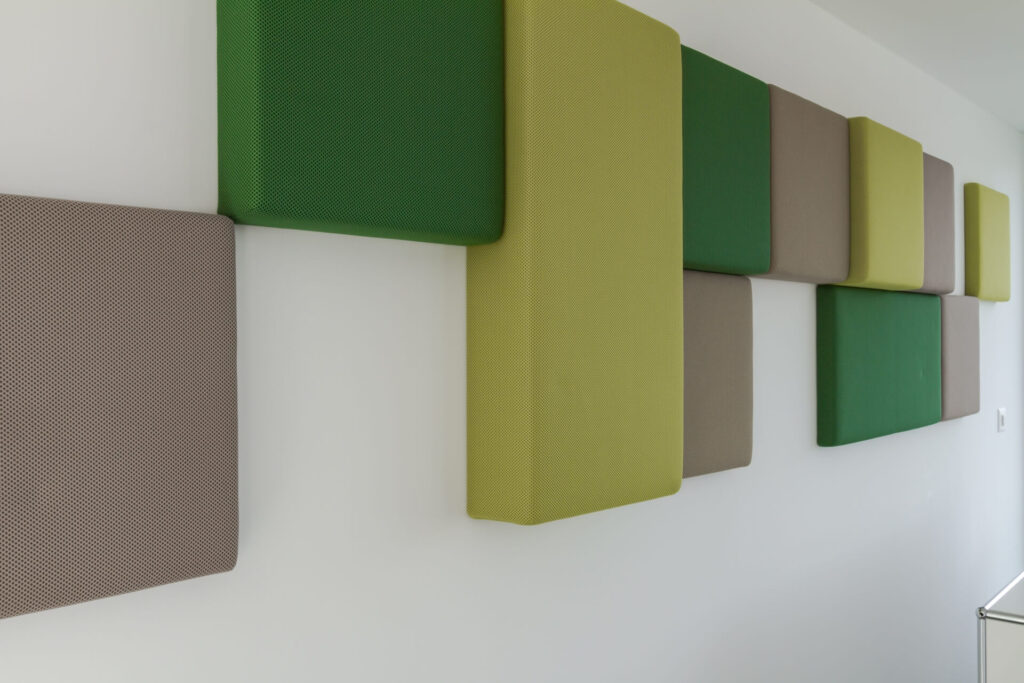 Seitliche Perspektive von 12 rechteckigen und quadratischen Akustikelementen (von Bellton AG), die in verschiedenen Grüntönen, asymmetrisch an einer weissen Wand angeordnet sind.