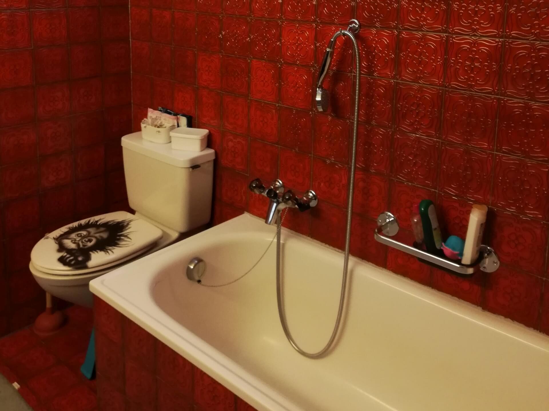 40-jährigen Badezimmers, mit roten, quadratischen Kacheln an Wand und Boden. Badewanne eingekleidet mit den roten Kacheln, das WC mit einem aufgesetzten Spülkasten und das Fenster mit Vorhang.