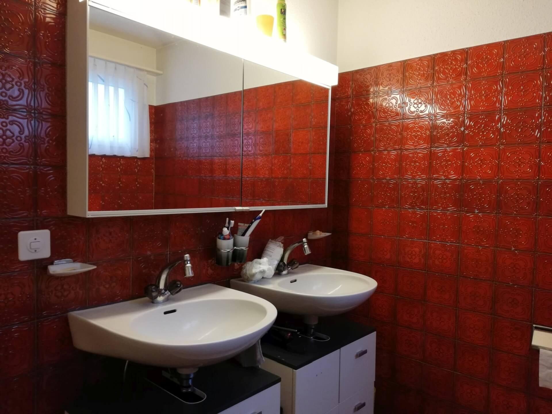 40-jähriges Badezimmers, mit roten, quadratischen Kacheln an Wand und Boden. Zwei einzelne Waschtische nebeneinander, ein breiter Spiegelschrank und zwei am Boden stehende Unterbauschränke.
