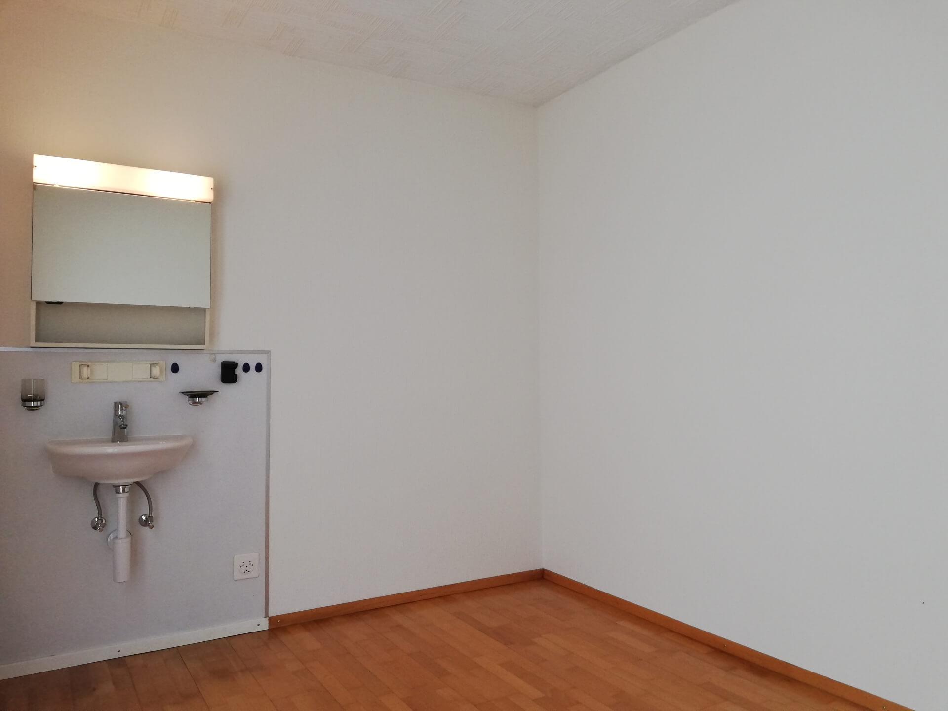Aufnahme einer Ecke des bestehenden Zimmers. auf der linken Bildseite befindet siche in alter, weisser Waschtisch und Haltevorrichtingen für Zahnglas und Seife. Darüber ist ein Spiegelschrank mit Licht montiert. Der Rest des Raumes ist leer. Der Boden ist aus braunen Parkett mit entsprechenden Sockel, die Wände sind weiss verputzt. Die Decke ist ebenfalss weiss und besteht aus Schallelementen mit Streifenmuster.