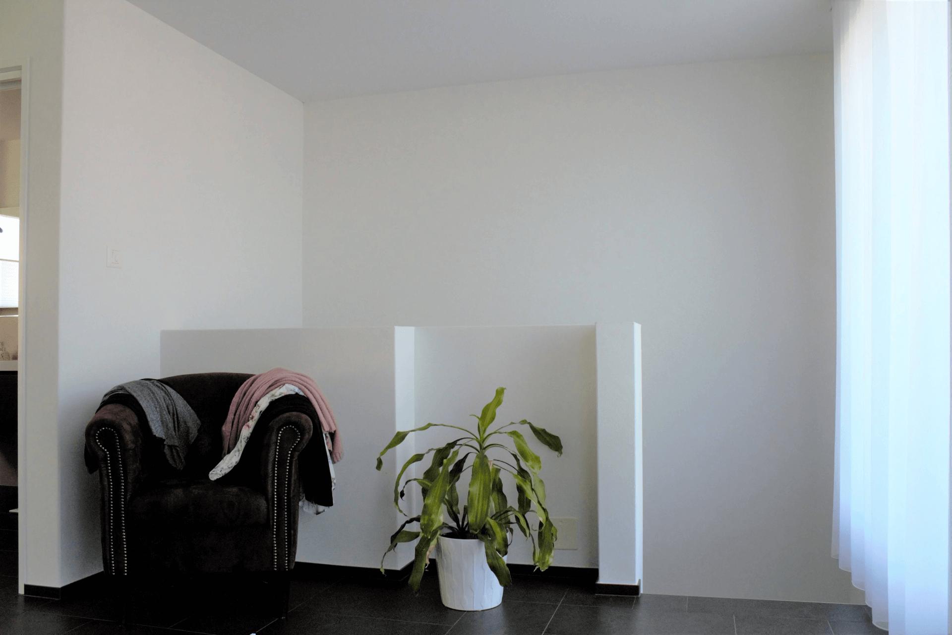 Bestehender Eingangsbereich des Schlafzimmers mit dunklen Feinsteinzeug Keramikplatten und weiss verputzten Wänden. Das Treppenhaus und das Schlafzimmer werden durch eine ca 80 cm hohe, weiss verputzte Brüstung getrennt. Keine durchgehenden Wände und / oder Türen. Möbliert ist dieser Bereich mit einem dunkelbraunen einplätzigen Sessel aus Stoff und einer rund 60 cm hohen Zimmerpflanze mit länglichen grünen Blätter in einem weissen Topf.