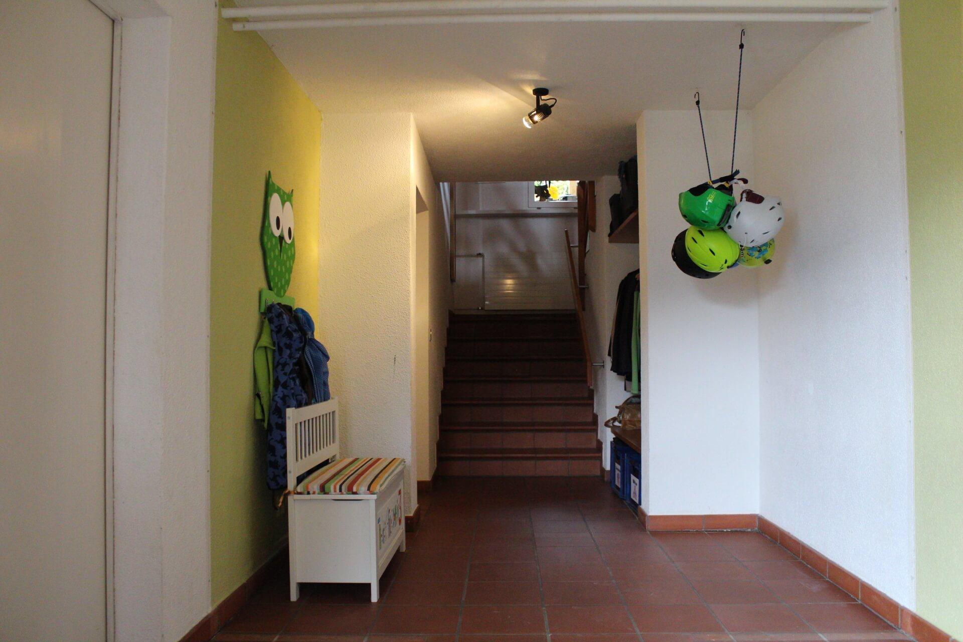 Eingangsbereich im Baustil der 80er Jahre. Ein länglicher, dunkler Raum der mit einer einzelnen Spotleuchte ausgeleuchtet wird, dessen Ende zu einer Treppe führt. Der Boden wie auch die Treppe ist mit dunkelroten Tonplatten von ca. 20x20 cm versehen. Die Fugen zwischen den Platten sind 1 cm breit und bilden so ein quadratisches Raster über den ganzen Fussboden. Die Wände wie auch die Decke sind mit körnigem Abrieb verspachtelt. Auf der linken Seite erkennt man eine geschlossene Tür. Weiter über die linke Seite, befindet sich eine gelbliche Wand, an der eine Tafel, in der Form einer grünen Eule, befestigt ist. Diese dient mit ihren sechs Hacken als Garderobe und ist mit Kinderjacken behangen. Unter der Eulengarderobe steht eine längliche, weisse und fast kniehohe Truhe, die als Sitzbank dient. Gegenüberliegend befindet sich eine weisse Wand. Vor dieser hängen sechs Skihelme, die an einem Seil befestigt wurden, von der Decke. Weiter den Gang entlang Richtung Treppe erkennt man auf der rechten Seite eine offen gestaltete Garderobe. Am Ende des Raumes angekommen, führt eine Treppe mit sieben Stufen, auf ein Zwischenpodest.