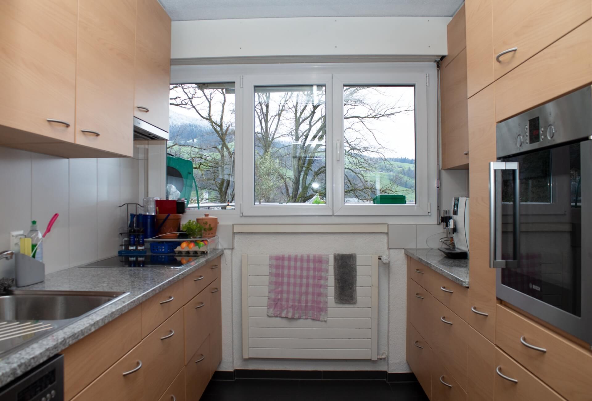 Perspektive einer bestehenden Küche. In der Mitte des Bildes befindet sich eine dreiteilige Fensterfront. Darunter ein Heizungsradiator mit darüber gehängten Putzlappen. Links und rechts der Perspektive befindet sich die bestehende Küche mit hellen Holzfronten mit grauen gebogenen Griffen und einer grau, weiss, schwarz maserierten Granitabdeckung.