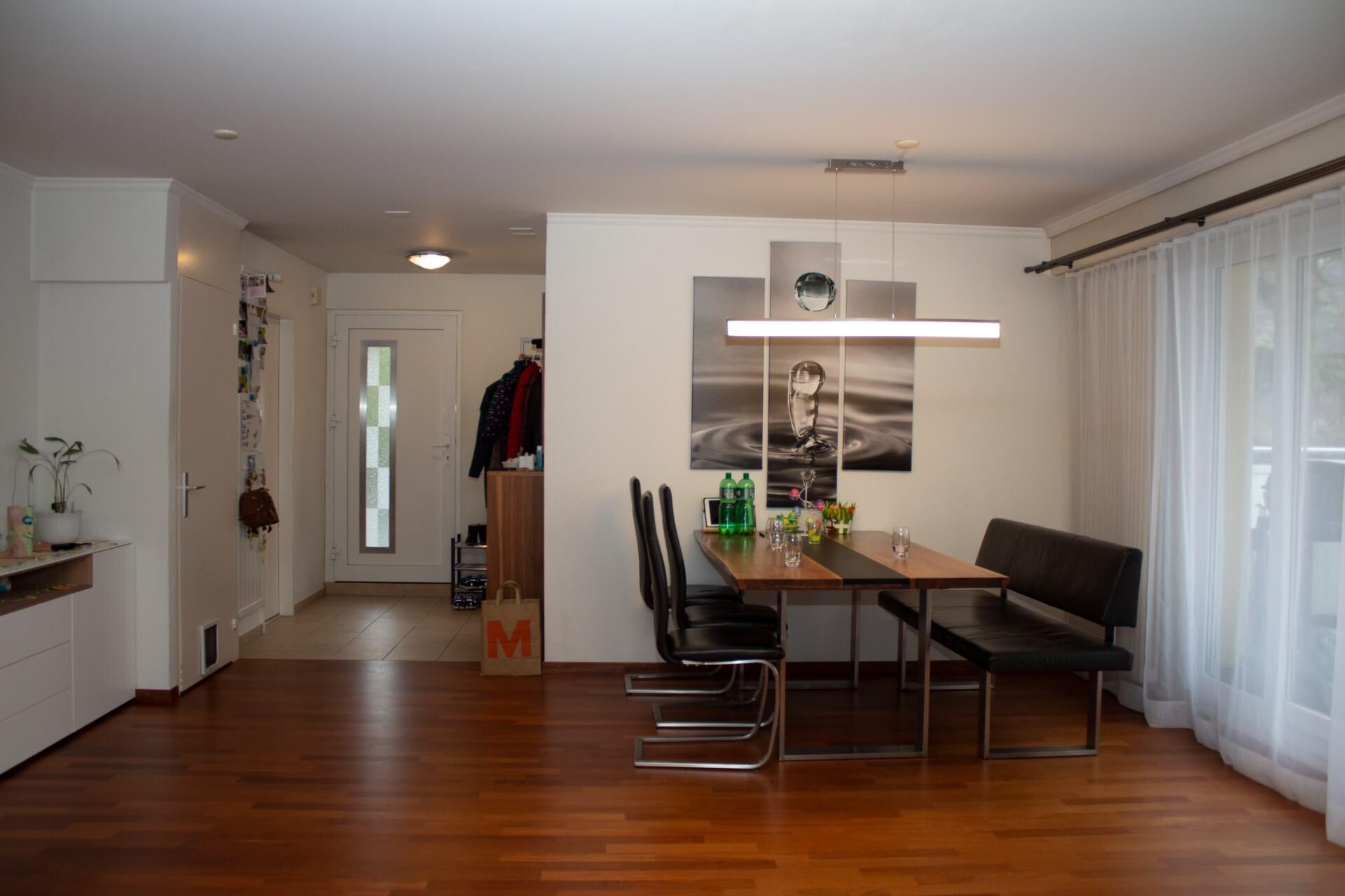 Perspektive von Wohnraum aus in Richtung Küchenbereich. Links befindet sich die weisse Eingangstür mit einem satiniertem Glaseinsatz. Rechts neben der Tür wurde eine Garderobenständer und darunterliegend ein dreistöckiger Schuhrost platziert. Weiter erkennt man eine Raum in Raum Situation in der sich die bestehende Küche befindet.  An der Wand die in den Wohnbereich zeigt, hängt mittig ein dreiteiliges, in schwarz/weiss gehaltenes Bild das einen aufschlagenden Wassertropfen zeigt. Direkt an der Wand steht ein massiver Holztisch in Nussbaumoptik der auf der linken Seite von drei schwarzen Stühlen und auf der rechten Seite von einem Bank umringt werden. Über dem Tisch ist eine geradlinige Leuchte montiert.