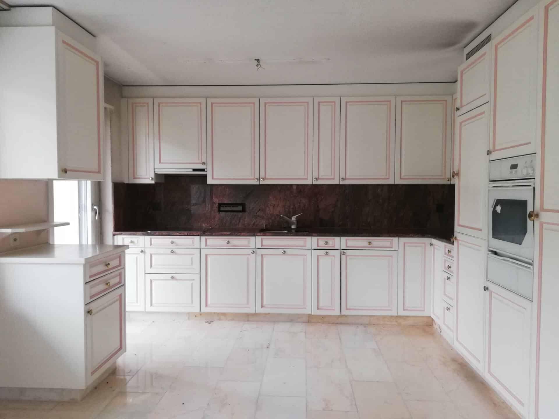Foto von bestehender Küche. Eine Weiss / Altrosa gehaltene L-Küche im Landhausstil. Die bestehende Granitabdeckung ist in der Farbe Terrakotta gehalten und hat eine schwarze Maserierung und Graniteinschlüsse. Auch das Rückschild ist mit dem selben terrakotta- / schwarzfarbenen Granit ausgebildet. Der Boden besteht aus hellem Marmor, der eine Maserierung in Altrosa aufweist.