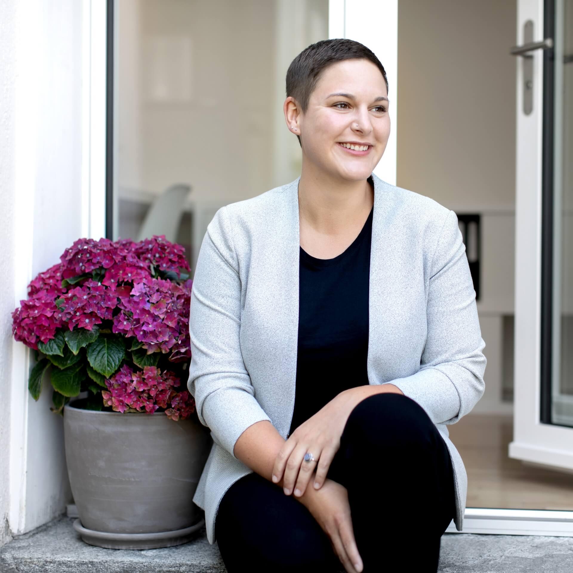 Portraitaufnahme von Katja Meier, der Inhaberin von der planen eintichten gestalten gmbh. Sie trägt dunkle Kleider und einen hellen Blaizer, sitz auf der Steintreppe vor dem Büroeingang, hat Ihren Kopf leicht zur Seite gedreht und lächelt freundlich.